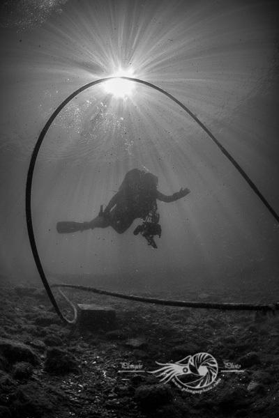 Les lignes créées par le câble crée un cadre au centre duquel le plongeur se trouve. Le soleil et ses rais de lumières ajoute au contraste de la photo.